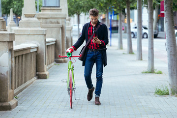 Stylish man with bike using cell phone as walking the street.