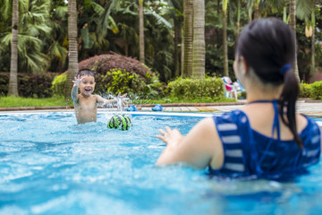 little asian boy having fun with his mother in the swimming pool
