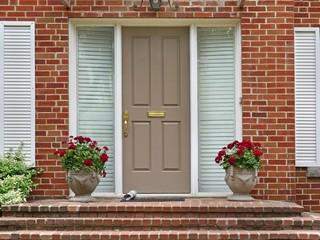 front door with newspaper and pots of geraniums
