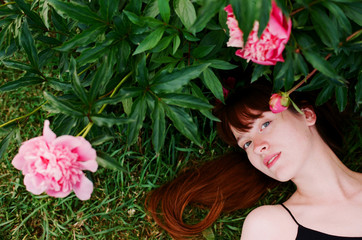 Young woman lying at peonies garden