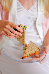 Anonymous blonde woman eating homemade sandwich for breakfast