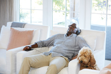 African American Senior man listening to music on a smart phone sitting on the couch at home