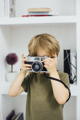 Young cute boy with film camera