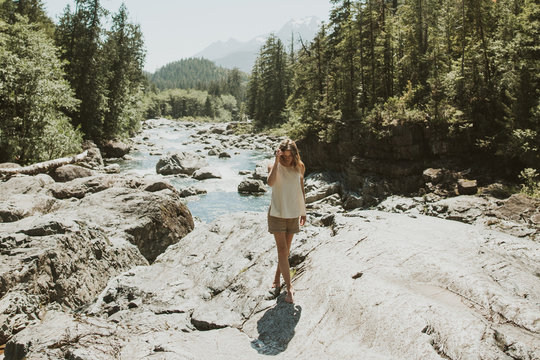 young woman walks on rocks near river