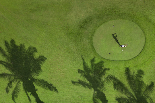 A male gold player swings out at tee off seen from above. his shadow displays perfect form.