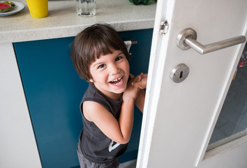 Smiling Toddler Hiding In The Kitchen