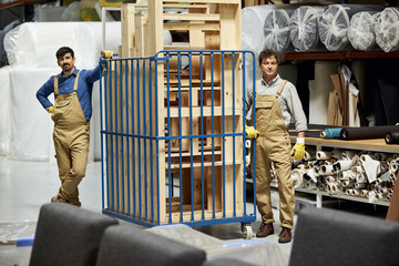 Confident Workers Standing By Trolley With Stacked Wooden Frames