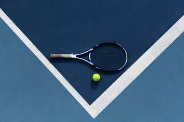 Tennis ball and racket on corner of court