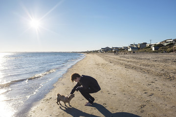 A boy takes his dog for a walk on the beach in winter.