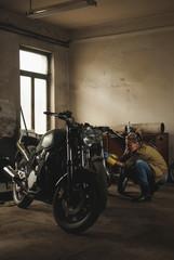 Young female working on restoration of old /vintage motorbikes in old rusty motorbike garage/workshop