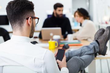 Overshoulder of businessman using mobile phone at desk in office.