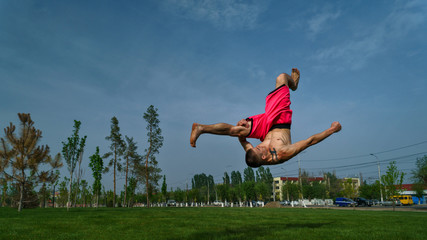 Tricking on lawn in park. Man does somersault ahead. Martial arts and parkour. Street workout.