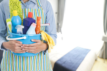 woman with cleaning equipment ready to clean house on bedroom background