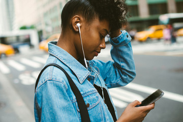 Young woman playing music on cell phone