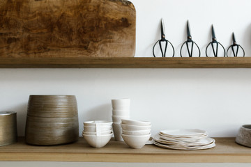 wood shelves of ceramics, scissors and cutting boards on white wall of curated shop