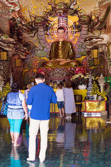 Tourists looking Altar and Buddha statues inside of  temple
