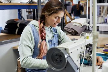 Female Worker Stitching Textile In Sofa Workshop