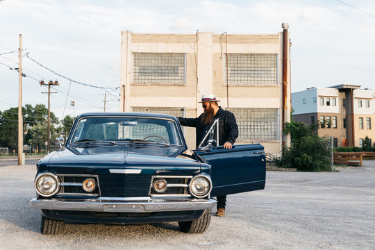 male with beard getting out of classic vintage retro car at sunset in front of building
