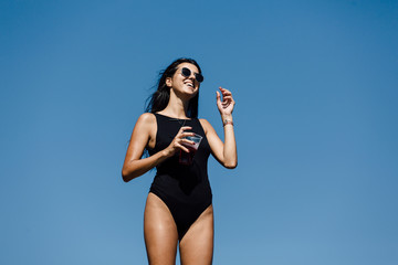 Portrait of attractive woman in black bikini drinking juice on the rocky shore