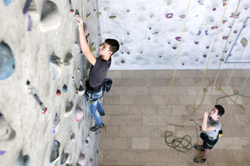 Two teenager friends rock climbing on an indoor wall