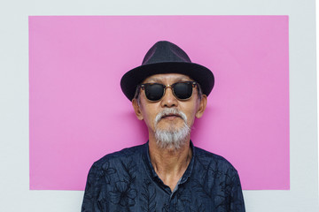Senior asian man portrait on pink background
