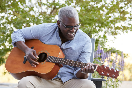 Closeup portrait of African American Senior man playing guitar and smiling outside