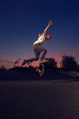 Male skater performing midair kickflips in the twilight