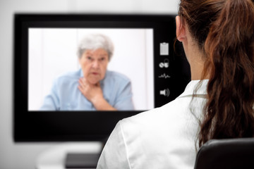 Kranke Patientin in der virtuellen Sprechstunde am Monitor, Fernbehandlung und Telematik im Gesundheitswesen