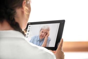 Diagnose und Sprechstunde über das Internet, Ärztin hält Tablet mit Patientin und Icons