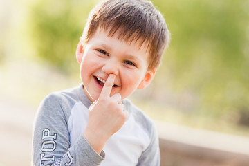little funny boy picks his finger in the nose outdoors