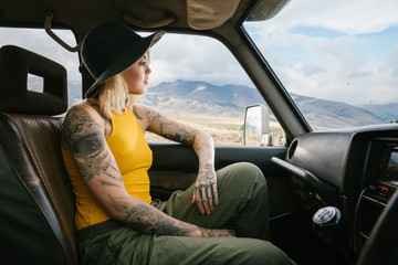 young tattooed blonde woman sitting in the car