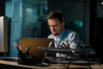 Frowning mad man working in office and having problems with laptop in disfunction