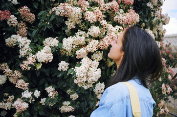 Attractive young woman stopping to smell the flowers