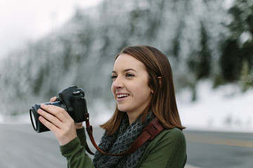 Woman Smiling and Taking Photographs with DSLR
