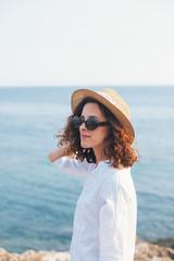 Woman standing on rocks near the sea
