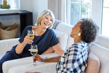 Senior women friends talking and drinking wine in living room at home
