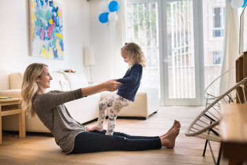Daughter and mother playing on the floor at home