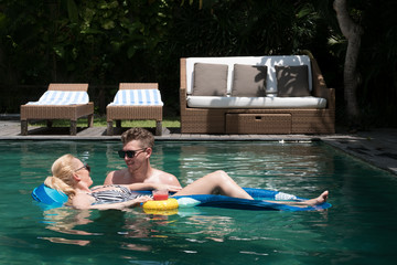 Young couple hanging out in pool together