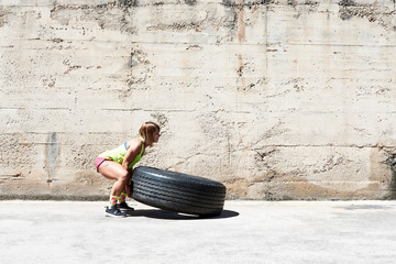 Strong woman lifting tire in sunlight.