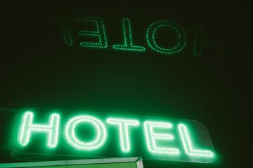 Green hotel sign at night.