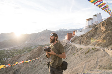 Man standing on peak and taking pictures with camera of Buddhism monastery on top of the mountain