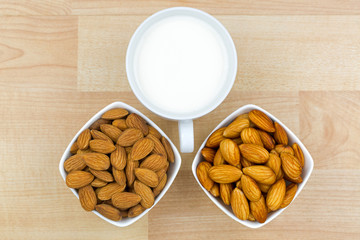 Dried and soaked Shelled Almond with cup of Almond Milk on wooden background