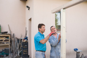 Men consulting about building wooden structure outdoor