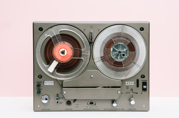 Vintage reel to reel in front of a pink background