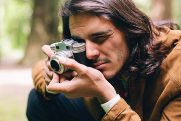 Young man taking photos with vintage camera in the woods.