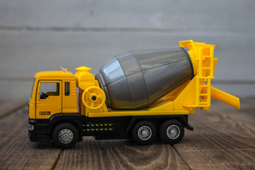 yellow toy concrete mixer on a wooden background
