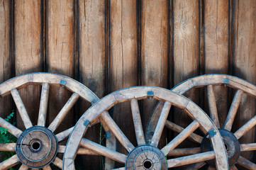 three old wooden wheels from carts on a log wall background