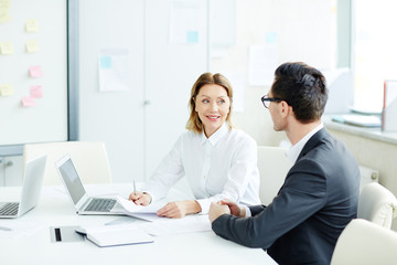 Female and male office workers sitting at desk in office room on business meeting looking at each other