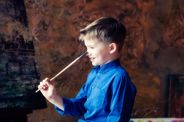 The boy draws and plays with a brush