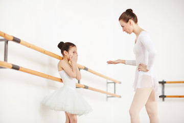 Ballerinas in white clothes and tutu staying in dancing studio at wooden machine and discussing
